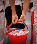 Two young men carrying a ice bucket to assist the bullring during the San Fermin Festival, on July 12, 2012, in Pamplona, northern Spain. The festival is a symbol of Spanish culture that attracts thousands of tourists to watch the bull runs despite heavy condemnation from animal rights groups . (c) Pedro ARMESTRE