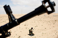 A man prays as he joins the front at Ajdabiya. A gun is seen in the foreground. On 17 February 2011 Libya saw the beginnings of a revolution against the 41 year regime of Col Muammar Gaddafi.