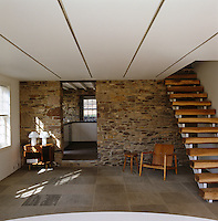An open wooden staircase ascends from a Japanese blue slate floor in this room with a rough stone wall