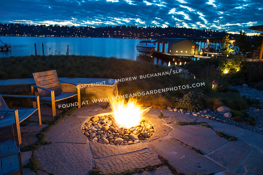 A firepit built into the stone patio of a waterfront home