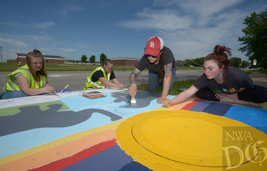 NWA Democrat-Gazette/BEN GOFF @NWABENGOFF<br /> Anya Bruhin (second from right), Pea Ridge Middle School art teacher, helps students from her 8th grade elective art class Kailey King (from left), Sadie Prince and Kyleigh Box paint their design Monday, May 15, 2017, as Pea Ridge Mayor Jackie Crabtree stops by to take a look, along Weston Street in front of the school in Pea Ridge. Students in the class partnered with UpStream Art to learn about water quality issues before working in small groups to designs and paint murals on six storm drains near the school.