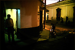 A shopkeeper outside his shop at dusk in Xela, Guatemala.