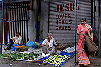 Vegetable sellers ply their trade on a road in Dharavi on 21st Oct 2006. Behind a sign proclaims the power of Jesus. Dharavi is celebrated as being a community of different faiths.
