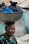 A woman carries a basin on her head as she walks in Batey Bombita, a community in the southwest of the Dominican Republic whose population is composed of Haitian immigrants and their descendents.