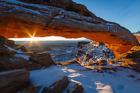 A beautiful Winter sunrise and starburst at Mesa Arch in Canyonlands National Park after a fresh blanket of snow covered the desert floor.