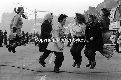 Shrove Tuesday Skipping, Scarborough, Yorkshire. England 1974.<br /> The merriment and feasting connected with Shrove Tuesday derive from it being the last day before the Lenten fast that begins on Ash Wednesday. Its date depends on Easter Sunday, which is the first Sunday after the full moon, and can fall any time between 2 February and 8 March. As its name commemorates, Shrovetide covers the three days, Sunday, Monday and Tuesday when one is<br /> expected to confess one's sins, or be 'shriven'.<br /> <br /> As a compensation for the earnest time ahead, games and food prohibited during Lent were indulged in with a particular fervour. Pancakes were favoured because they used forbidden ingredients such as eggs and fat. Also, the custom of bell-ringing at Shrovetide, no doubt originally a signal for parishioners to attend confession, became a vigorous activity in its own right.<br /> <br /> In Scarborough the curfew bell, which hung at the entrance to the Hospital of St Thomas the Martre, used to be rung every morning and evening at six o'clock, and in particular at twelve noon on Shrove Tuesday as a signal to start frying the pancakes.<br /> In 1861, when the Hospital was demolished, the bell was moved to<br /> the town museum, and, since then, with the exception of the years 1939-45, the Pancake Bell, as it is now called, has been rung annually at midday by the museum staff.<br /> <br /> According to a nineteenth-century account, Shrove Tuesday in Scarborough was known as 'Ball Day', and from time immemorial balls have been tossed about on Southsands. However, for some time skipping has been the most favoured custom. In 1974 local schools still have a half-holiday, and hundreds of children, parents and<br /> adults gather after lunch on the promenade at Southsands to skip with huge ropes until dusk.<br /> <br /> A new  Pancake Bell was errected in the town in 1996 and the celebrations are now opened by the Town Cryer and the Mayor in full regelia now rings the Panc