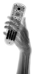 X-ray image of hand and remote control (black on white) by Jim Wehtje, specialist in x-ray art and design images.
