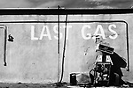 "a broken gas pump against an adobe wall with words ""last gas"" written on the wall comments on the state of energy supply and demand in the world in the 21st century, big chief gas station, san ysidro, new mexico, usa"