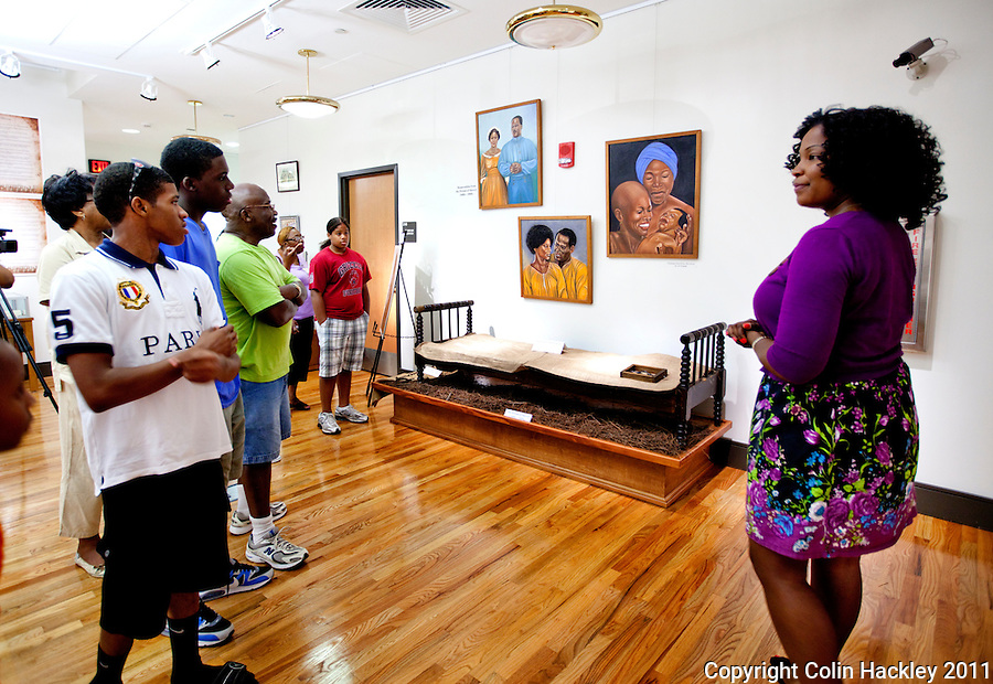SLAVE BREEDING BED: Tanisha Matthews, right, talks about a slave breeding bed as she leads a tour for the Robinson family reunion through The Black Archive's Slavery in the Old South collection in Tallahassee..COLIN HACKLEY PHOTO