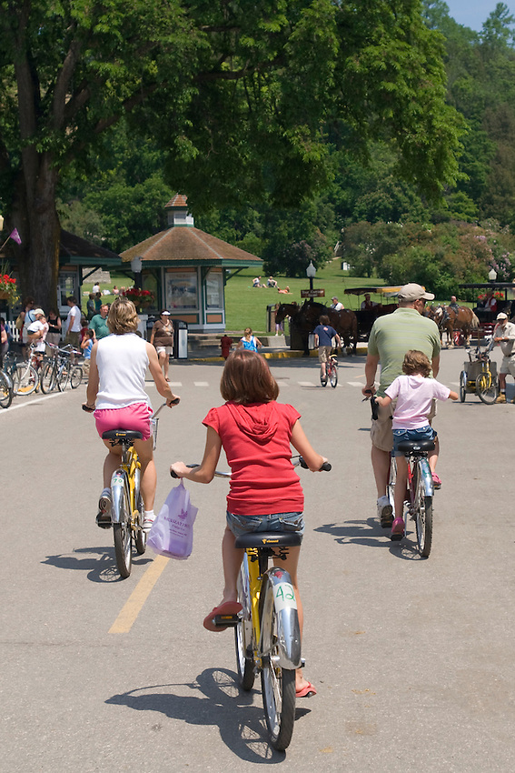 A family bikes down a street on Mackinac Island in Michigan.