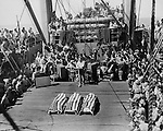 The flag-draped bodies of three Marines killed at Tarawa rest on a hatch cover during funeral services aboard a transport. They were buried at sea following the service.