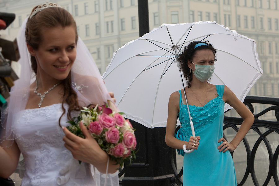 Moscow, Russia, 07/08/2010. .A woman at a wedding party in central Moscow wears a mask against the worst smog so far in the record high temperatures of the continuing heatwave. Peat and forest fires in the countryside surrounding Moscow have resulted in the Russian capital being blanketed in heavy smog.