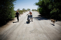 Niland, California, March 28, 2008 - Hitting the Road, Justin Davis pushes a motorcycle he traded for some mechanic work, with his dog Coco and friend Billy Williams.