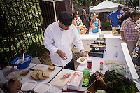 Chef Keith Grant prepares vegetable sandwiches at a cooking demonstration at the Fortune Society's Fortune Fresh farm stand at the Grassroots Farmers Market in Harlem in New York on Saturday, August 24, 2013. The Fortune Society develops programs, including Culinary Skills/Food Service Training, for former prisoners and young people involved in the criminal justice system preventing recidivism. (© Richard B. Levine)