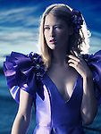 Beauty portrait of a young beautiful blond woman wearing a blue evening dress outdoors