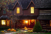 Renovated cabin into new home lit for halloween and welcoming neighbors, Midwest USA