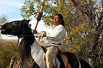 A Native American Indian riding horseback on a pinto horse with war markings in paint while trying to stop the horse