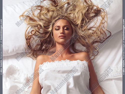 Closeup portrait of a beautiful sleeping young woman with long blond hair lying in bed