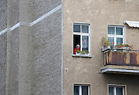 A woman looks out of the window of her apartment in an old housing block, formerly in East Berlin, on the corner of Wolliner and Bernauer Strasse. The Wall ran directly beside these housing blocks.