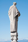A statue of a woman in a cloak looking over the city, on the roof of the Duomo (Cathedral) in Milan, Italy.