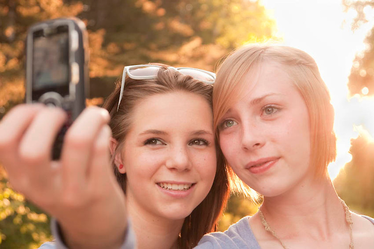 Teenage girlfriends taking a picture of themselves on a phone outside.