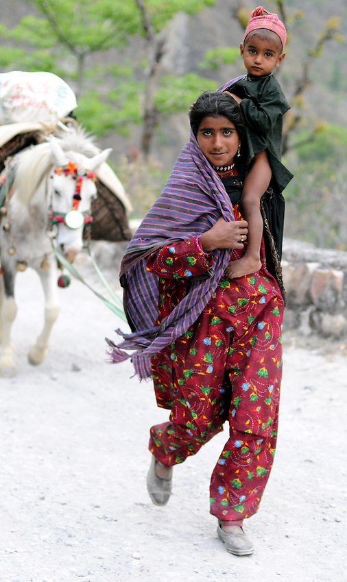 Goku, 14 years old, carries Yasin, 2, while leading a pack horse.