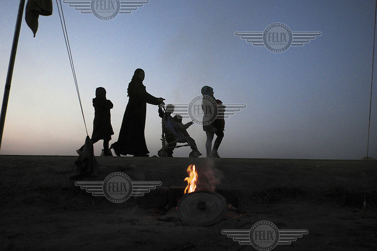 A refugee family walking near the makeshift refugee camp at Idomeni. Around 14,000 people were stranded in the camp which the authorities have since closed and distributed the occupants among several official camps around the country.