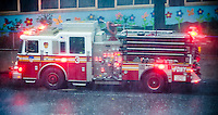 An FDNY truck answers a call outside a building in the Chelsea neighborhood of New York during a summer torrential downpour on Wednesday, July 18, 2012.  (© Richard B. Levine)
