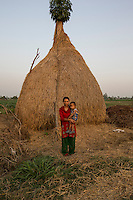"Nepal - Meghauli - Sanju Bhatta, 29, in her house in the village of Meghauli, in the Central district of Chitwan. Bhatta lives alone with her four kids, aged from ten to two, after her husband Rameshwar Bhatta left to work in Qatar as a driver one week ago. The couple has been married for 11 years. Rameshwar left Nepal to repay the loan the family took to build their house, leaving Sanju to look after their fields and small store. ""I am alone. I have to cook, farm, feed the animals and raise the kids all by myself. They frequently ask me about their father"" she says. Rameshwar frequently calls her. ""The only think he complains about is that he has to work so hard for such a small amount of money""."