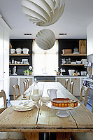 A pitch pine table above which hangs a pair of 1960s style pendant lights takes centre stage in the kitchen