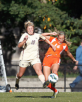 University of Miami forward Ava Ambrose (16) clears the ball as Boston College midfielder Gibby Wagner (10) defends..After two overtime periods, Boston College (gold) tied University of Miami (orange), 0-0, at Newton Campus Field, October 21, 2012.