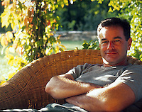 Portrait of a man with a happy, content expression as he rests under an arbor.