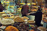 A woman making a selection of spices to a shopkeeper in the Spice Market in Istanbul, Turkey