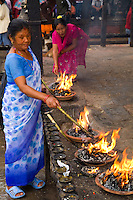 Woman making fires to worship in Hindu religion at Nyatapola Temple in village of Bhaktapur a town near Kathmandu Nepal