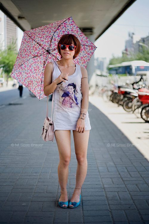 Shenyinying, a clothing assistant, age 23, poses for a portrait in Beijing. Response to 'What does China mean to you?': 'To me China is just a big family. The place where I was born and raised. I owe everything to my homeland.'  Response to 'What is your role in China's future?': 'Put in more of an effort in support of my country's development of clothing.'
