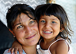 """THIS PHOTO IS AVAILABLE AS A PRINT OR FOR PERSONAL USE. CLICK ON """"ADD TO CART"""" TO SEE PRICING OPTIONS.   Mirjava Memetovic holds her daughter Kristina. They live in Palilula, a neighborhood of Belgrade, Serbia. They are Roma, also known as Gypsies, and were expelled in 2012 from the center of Belgrade to make way for new apartments and office buildings. Because Memetovic had no identity documents, she was sent with her daughters to her native village in the south of the country, but soon returned as she had no way to survive there. She and her daughters beg for money at a fast food restaurant near their squatter settlement."""