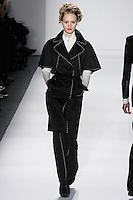 Model walks runway in a black loro piana wool/angora capelet-trench+bootleg pant w/ivory hand top-stitching, ivory handloomed cashmere/silk zippered ribbed turtleneck, from the Zang Toi Fall 2012 &quot;Glamour At Gstaad&quot; collection, during Mercedes-Benz Fashion Week New York Fall 2012 at Lincoln Center.