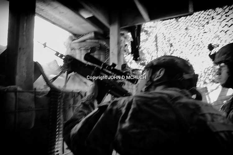 US soldiers from 2nd Platoon, 2/27 Infantry, 25 Infantry Division, shoot at known Taliban positions in an attempt to disrupt their enemy's freedom of movement at Checkpoint 2.5, beside Saw village, in Kunar province, 01 Dec 2011. (John D McHugh)