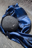 A granite boulder is cushioned on a length of blue Jacquard cotton and polyester