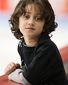 Northeastern's Ario Nour helps out from the bench during warmups. - The Boston University Terriers defeated the visiting Northeastern University Huskies 5-0 on senior night Saturday, March 9, 2013, at Agganis Arena in Boston, Massachusetts.