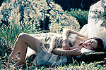 Female youth wearing a summer dress lying in the sun alone in rural setting