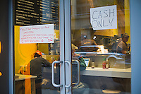 A sign advertises The Melt Shop Emergency Cell Phone Charge Station at a Melt Shop restaurant in the Chelsea neighborhood in New York on Wednesday, October 31, 2012. Con Edison is estimating electricity will not be restored back to Lower Manhattan for several more days and a number of businesses are allowing people to charge their batteries.  (© Frances M. Roberts)