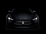Dramatic photo of a dark 2014 Maserati Ghibli S Q4 luxury car front view with shining headlights isolated on black background