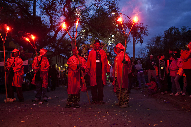 One of the oldest traditions of Mardi Gras, Flambeaux carrying flares preparing to parade during Mardi Gras in the Uptown area of New Orleans, Louisiana, USA.