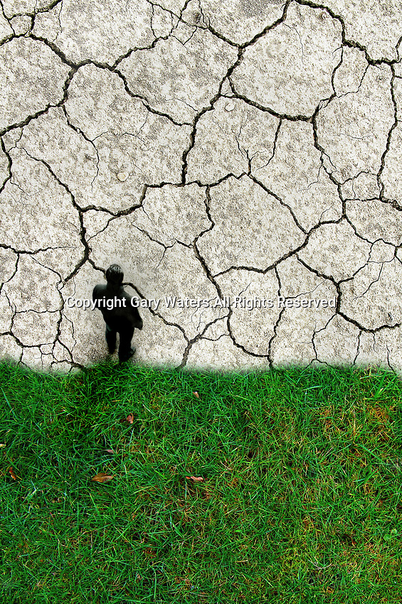 Overhead view of man standing at boundary between green grass and barren cracked earth