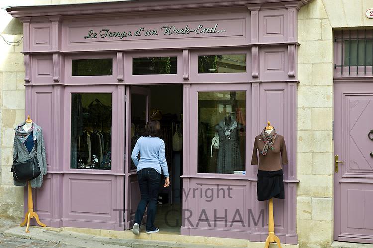 Customer enters ladies fashion shop Le Temps d'un Week-end in St Emilion, Bordeaux, France