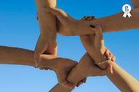 Group of five people connecting hands, on blue sky (Licence this image exclusively with Getty: http://www.gettyimages.com/detail/103810542 )