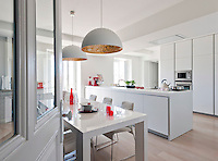 A pair of copper-lined pendant lights illuminates a white lacquered table in this contemporary kitchen/dining area