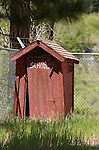 """Red wooden outhouse with cyclone fence, """"School"""" painted on the door, Colorado Rockys"""