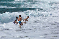 Three young boys having an exhilarating time playing in the breaking waves